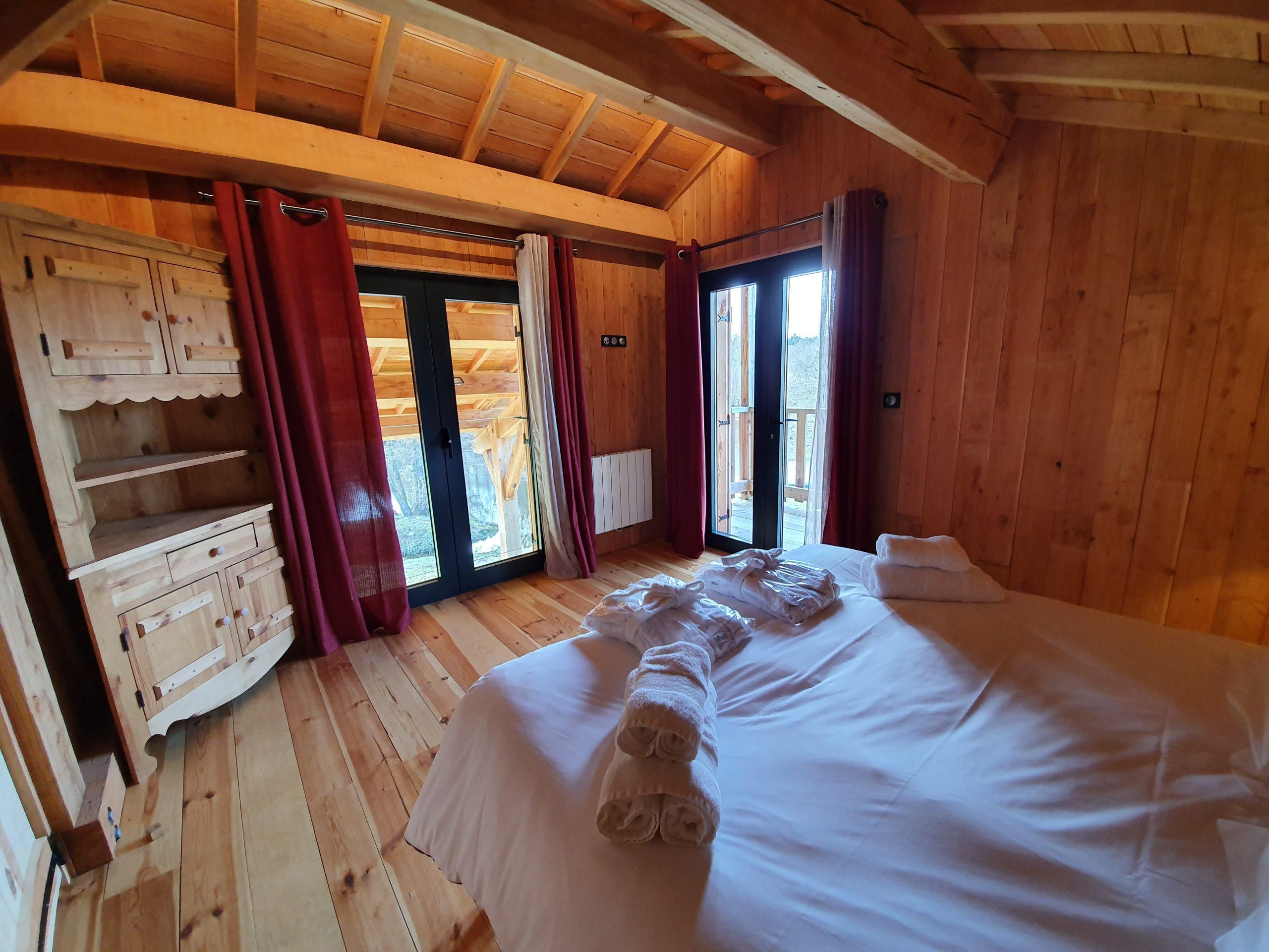 Chambre double avec balcon et vue sur l'étang du chalet